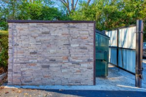 stacked stone dumpster enclosure with green dumpster and man door