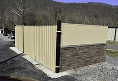 dumpster enclosure with stucco and ledge stone wainscot