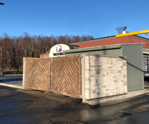 grey ledge stone dumpster enclosure with slanted wood gates in front of Taco Bell
