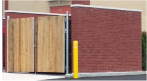 brick dumpster enclosure with wooden gate