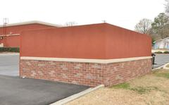 dumpster enclosure with brick panels and red stucco