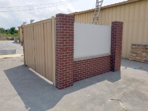metal dumpster enclosure with brick columns and half brick panel
